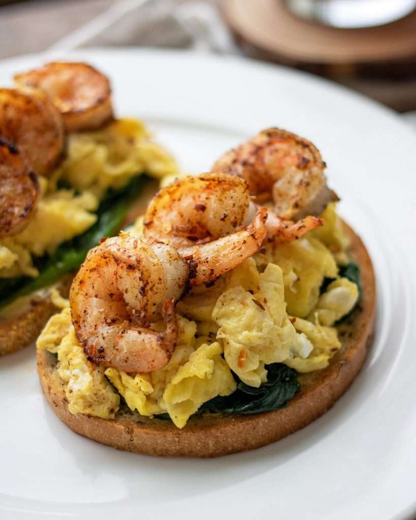 Sautéed shrimp, scrambled eggs, and spinach on open toast with a cup of tea