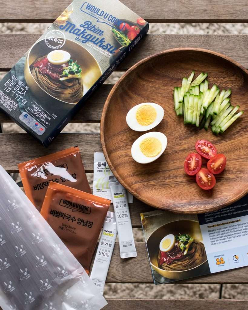 components of woulducook bibim makguksu kit with hard-boiled eggs, cucumber, and tomatoes