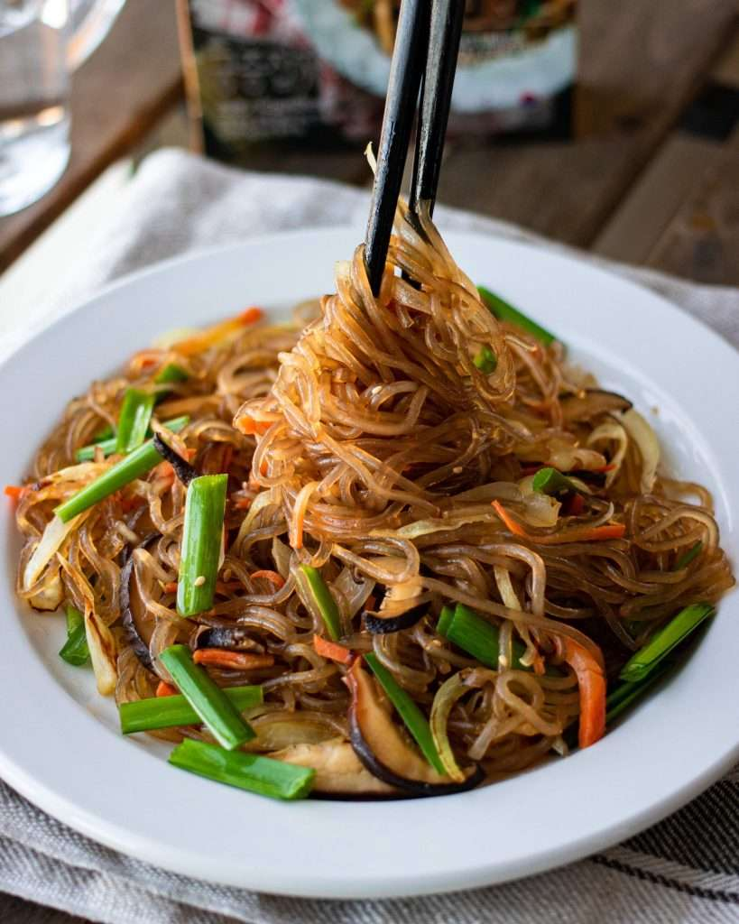 closeup of japchae korean glass noodles served on a plate